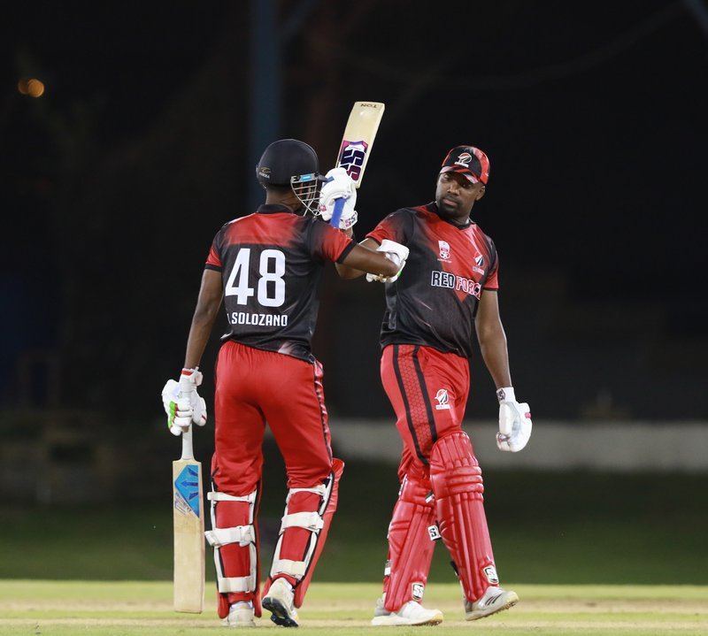 Darren Bravo,right, celebrates his century with T&T Red Force team mate Jeremy Solozano during the Colonial Medical Insurance Super 50 Regional Chmapionship match against the Winward Island Volcanoes at the Queens Park Oval,Port of Spain,Trinidad. .jpg
