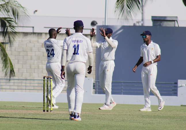 6 Kemar Roach celebrates taking a wicket with teammates.jpg