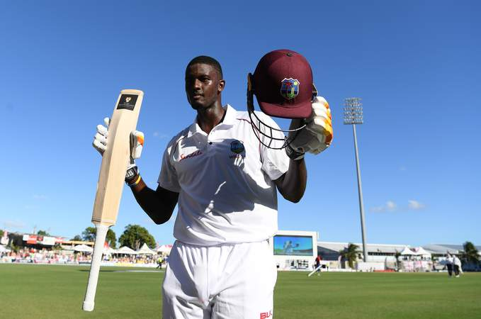 Jason Holder holds bat & helmet.jpg